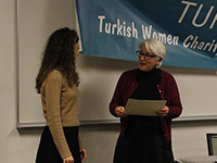 Turkcha's board member giving a thank you card to Dr. Piyale Comert